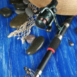 Fishing rod, gumboots and hat on wooden table close-up — Stock Photo #47552105