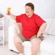Lazy overweight male sitting with glass of beer on couch and watching television — Stock Photo #47553081