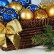 Christmas decorations in basket and spruce branches on table on bright background — Stock Photo #47553659