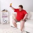 Lazy overweight male sitting with glass of beer on couch and watching television — Stock Photo #47555939