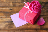 Pink gift with bow and flower on wooden table close-up — Stock Photo