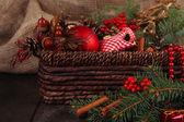 Christmas decorations in basket and spruce branches on table on sackcloth background — Stock Photo