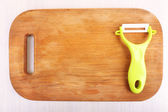 Vegetable peller and cutting board on wooden table — Stock Photo