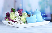 Composition with tea set and bouquet of beautiful spring flowers on tray, on wooden table, on bright background — Stock Photo
