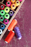 Multicolor sewing thread in wooden box, on wooden background, close-up — Stock Photo