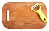 Vegetable peeler and cutting board isolated on white — Stock Photo
