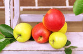 Beautiful still life with ripe sweet apples and leaves on brick wall background — Stock Photo