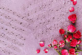 Beautiful pink dried roses on old wooden background with notes — Foto de Stock