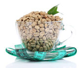 Raw green coffee beans in glass cup and measuring tape, isolated on white. Concept of weight loss — Stock Photo