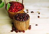 Fresh and dry cranberry in baskets on wooden table — Stock Photo