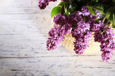 Beautiful lilac flowers in vase, on color wooden background — ストック写真