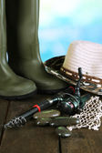 Fishing rod, gumboots and hat on wooden table on natural background — Stock Photo