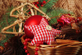 Christmas decorations in basket and spruce branches close up — Stock Photo