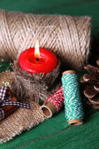 Composition with natural bump, candle, thread, cinnamon sticks on wooden background — Stock Photo