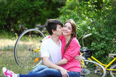 Young couple sitting in park with bicycles — Stok fotoğraf