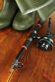 Fishing rod, gumboots and hat on wooden table close-up — Stock Photo