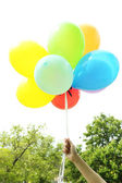 Balloons in hand, outdoors — Stock Photo