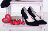Beautiful black female shoes and flowers on white background — Stock Photo