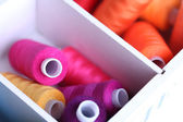Multicolor sewing thread in wooden box, close-up — Stock Photo