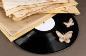 Old vinyl record with  old paper and butterflies, on brown background — Stock Photo