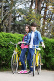 Young couple with bicycles in park — Stok fotoğraf