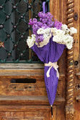 Beautiful lilac flowers in umbrella on old wooden doors — Stock Photo