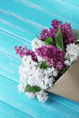 Beautiful bouquet of lilac flowers on color wooden background — Foto de Stock