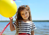 Beautiful little girl with colorful balloons on the beach — Stock Photo