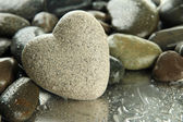 Grey stone in shape of heart, on light background — Stock Photo