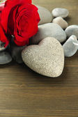 Grey stone in shape of heart, on wooden background — Stock Photo