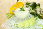Cucumber yogurt in glass bowl, on color napkin, on color wooden background — Stock Photo