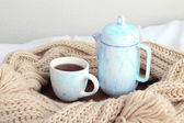 Cup and teapot with scarf on bed on wall background — Stock Photo
