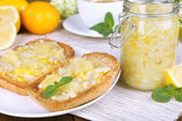 Delicious toasts with lemon jam on plate on table close-up — Stock Photo