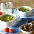 Tasty soup in saucepans on wooden table, close up — Stock Photo #47842551