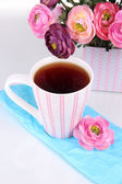 Fragrant tea with flowers isolated on white — Stock Photo