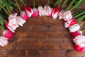 Beautiful tulips on color wooden background — Stock Photo