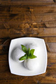 Tasty mozzarella cheese with basil on plate  on wooden background — Stock Photo