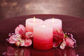 Beautiful candles with flowers on table on brown background — Stock Photo