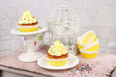 Tasty cup cakes with cream on wooden table — Stock Photo