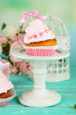 Tasty cup cakes with cream on blue wooden table — Stock Photo