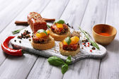 Composição de deliciosos sanduíches com salsicha de salame, folha de manjericão na tábua, sobre fundo de madeira — Fotografia Stock