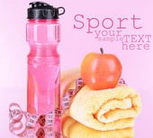 Sports bottle, apple,towel and measuring tape on pink background — Stock fotografie