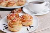 Tasty  puff pastry with apple shaped roses on plate on table close-up — Stock Photo
