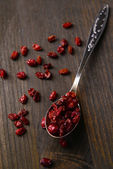 Spice barberry in spoon on wooden background — Stock Photo