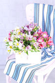 Beautiful bouquet of freesias in wooden box on chair in room — Stockfoto