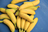 Bunch of mini bananas on color wooden background — Stock Photo