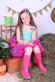Beautiful small girl in petty skirt on country style background — Stock Photo