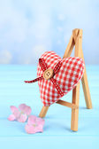 Beautiful heart  small decorative easel on blue background — Stock Photo