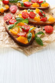 Tasty bruschetta with tomatoes, on table — Stock Photo