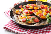 Tasty bruschetta with tomatoes in pan, on table — Stock Photo